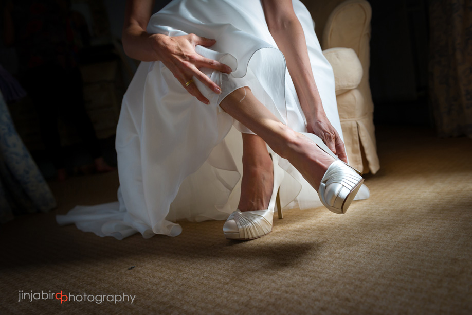 bride_putting_on_shoes_at_fawsley_hall