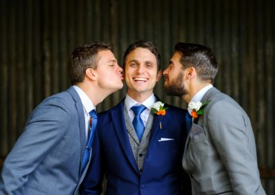 ushers-kissing-groom
