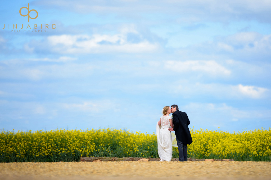 bride-and-groom-in-rapeseed-field-bassmead-manor-barns