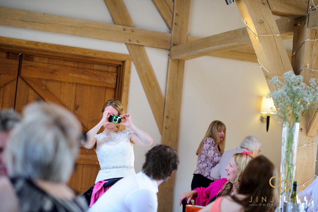 bride-taking-photo-bassmead-manor-barns