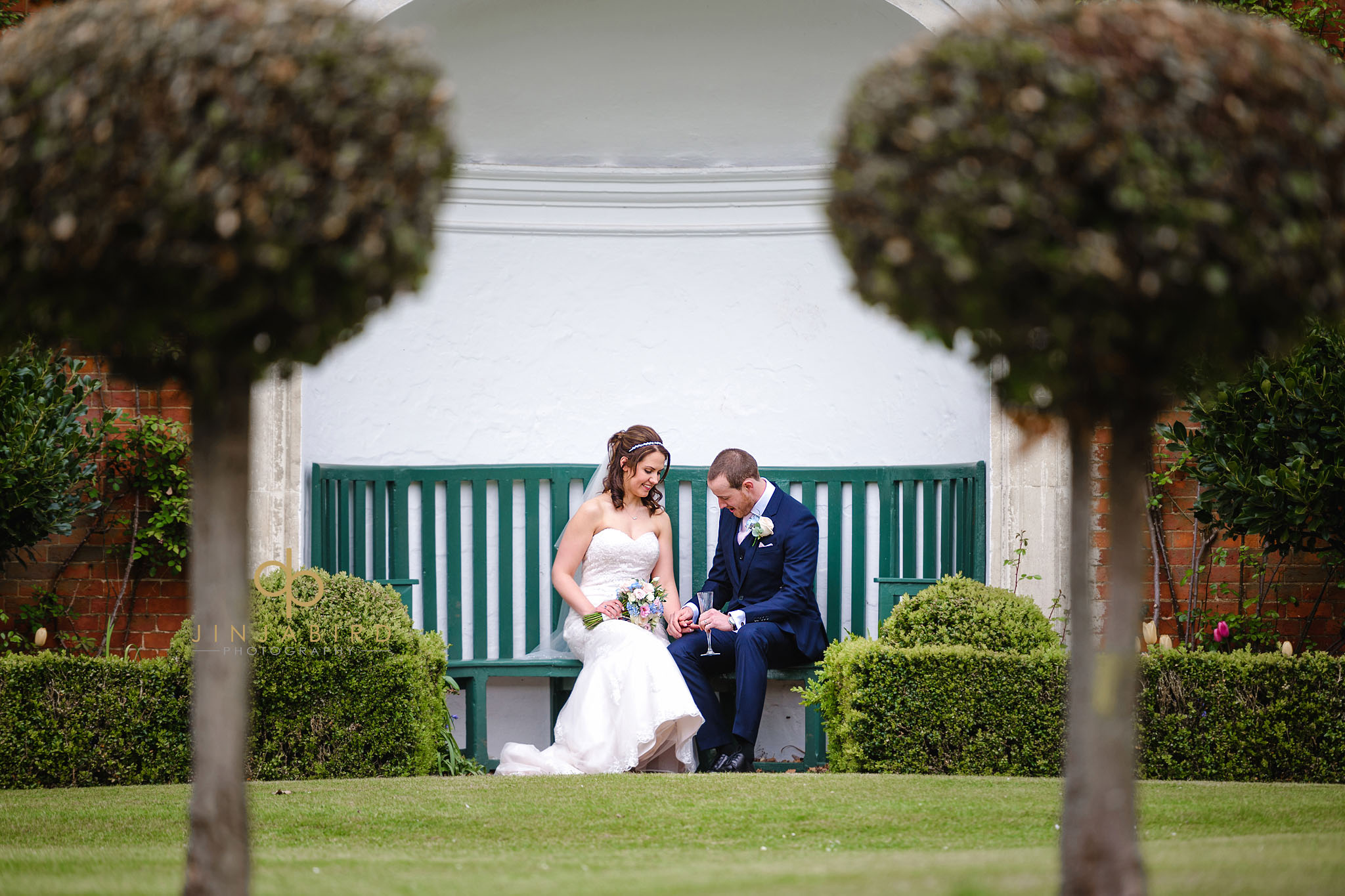 bride and groom sitting in garden chicheley hall