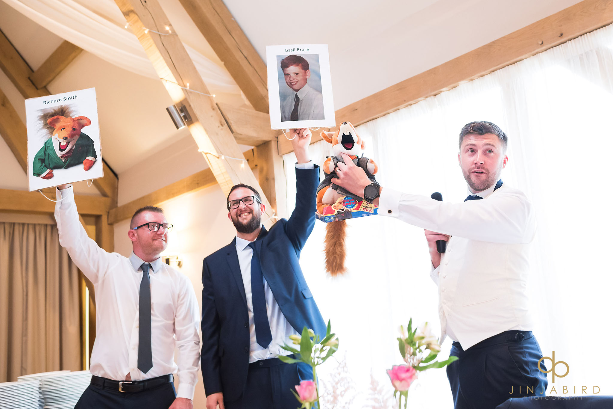 best men holding up pictures of groom
