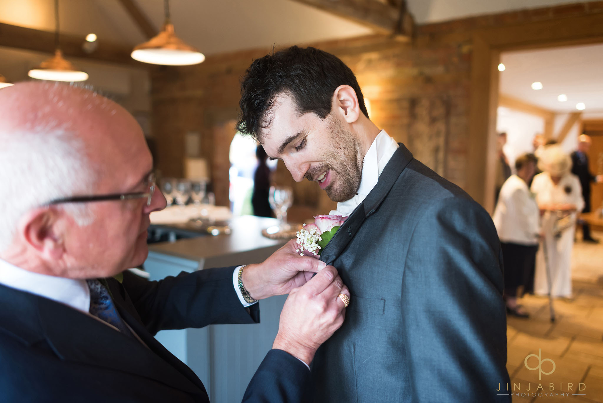 groom putting on buttonhole