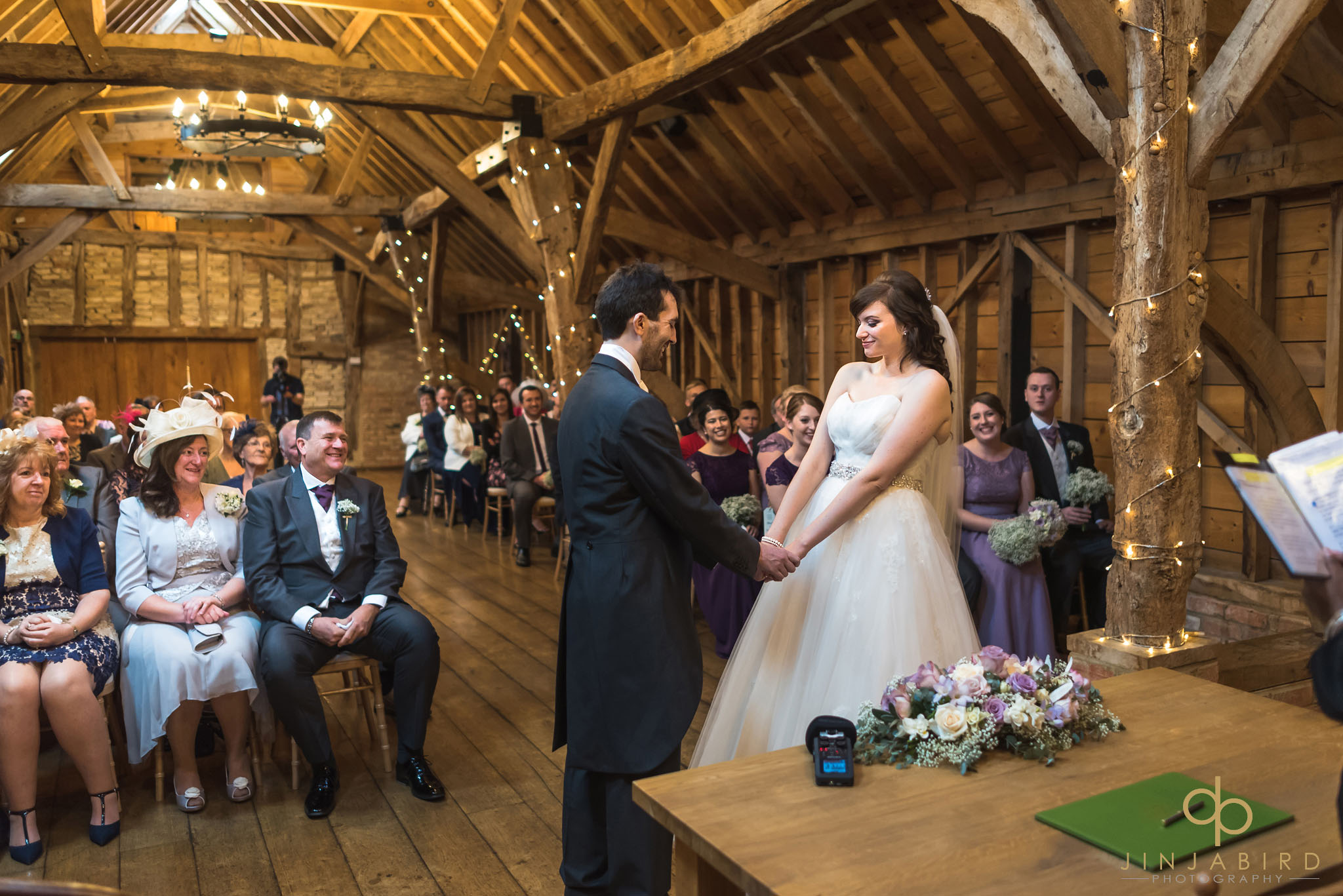 bride and groom holding hands in ceremony bassmead manor