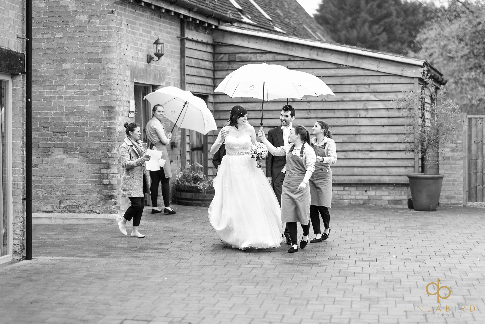 bride and groom walking in rain with umbrellas bassmead manor