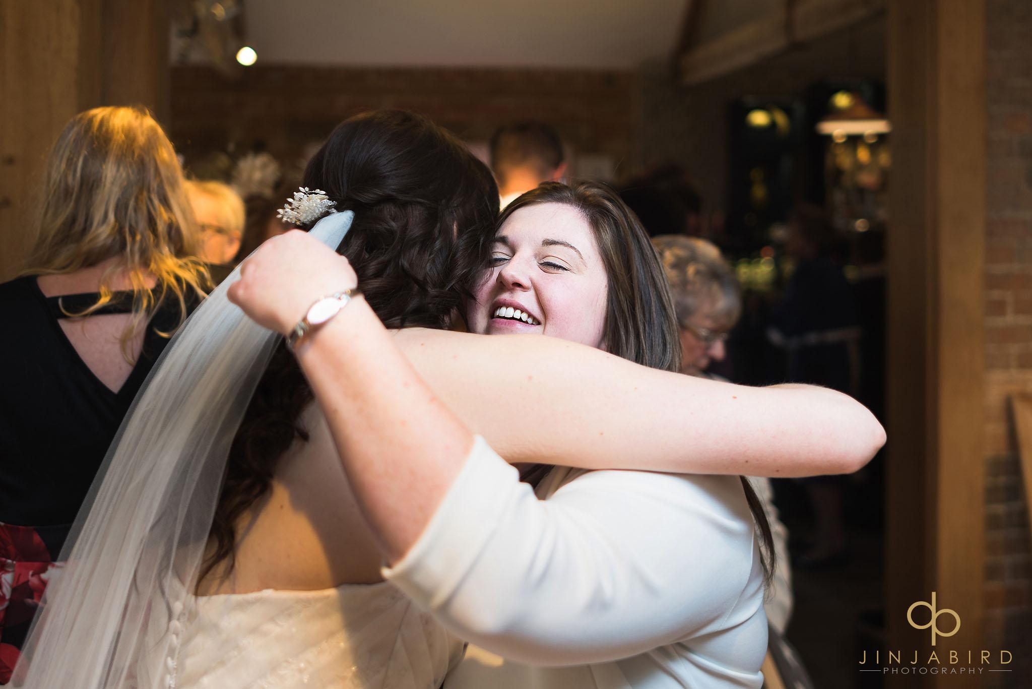women hugging bride