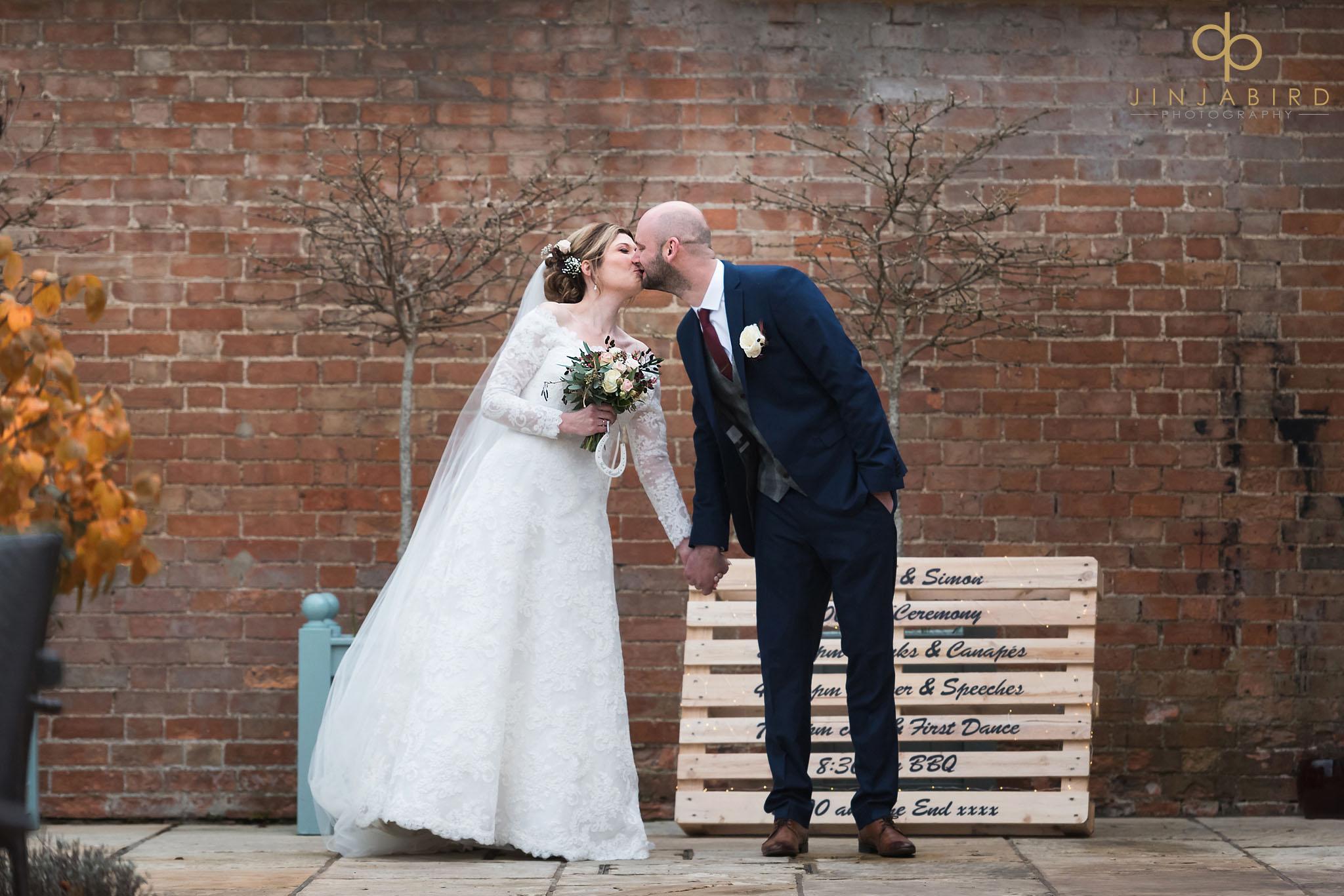 bride kissing groom in garden at bassmead