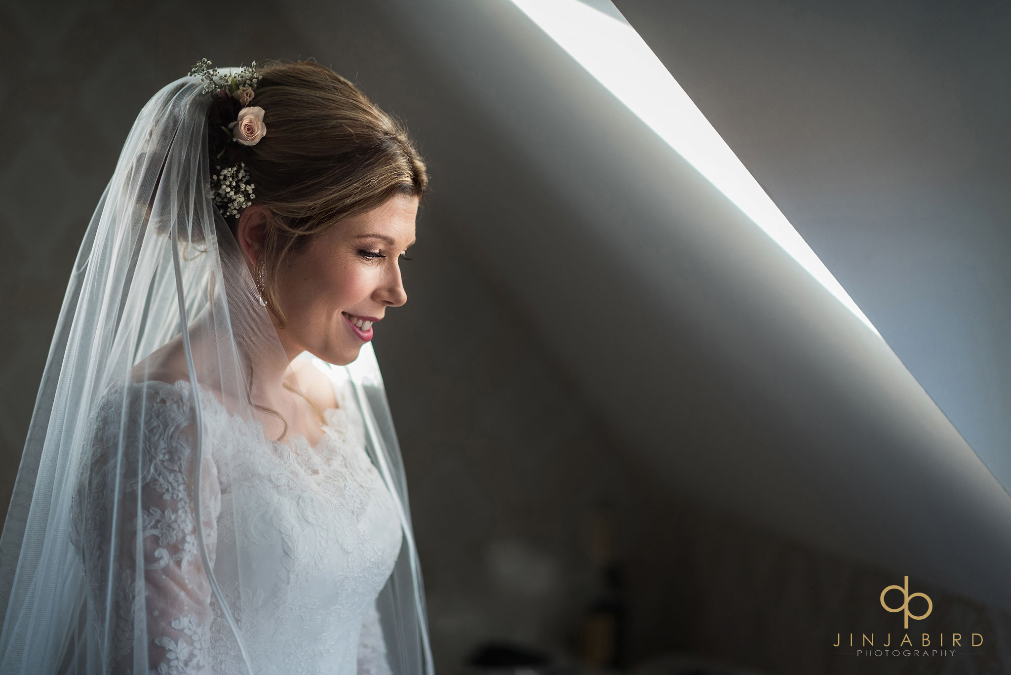 bride in veil looking out of window
