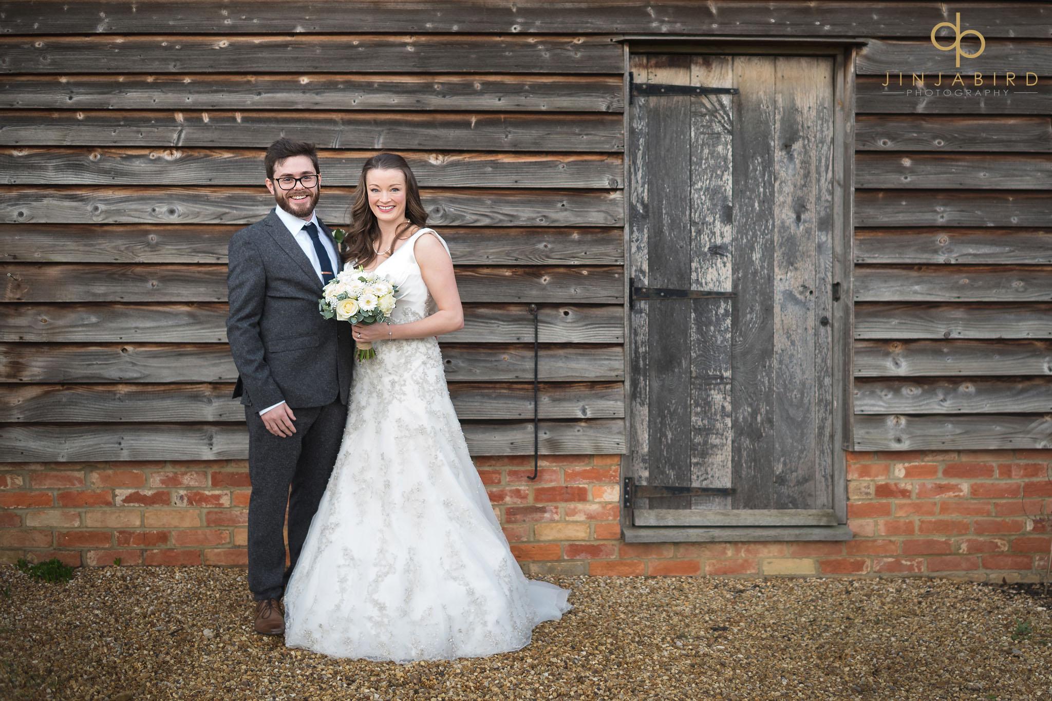 bride and groom outside rickety barn bassmead