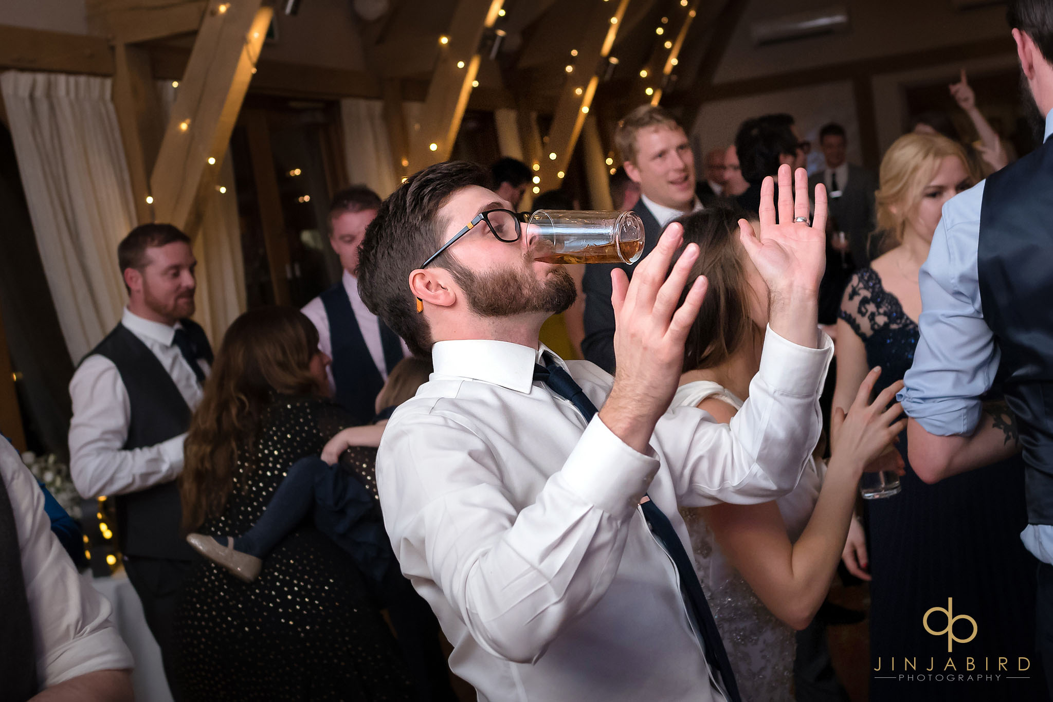 groom dancing with glass in mouth