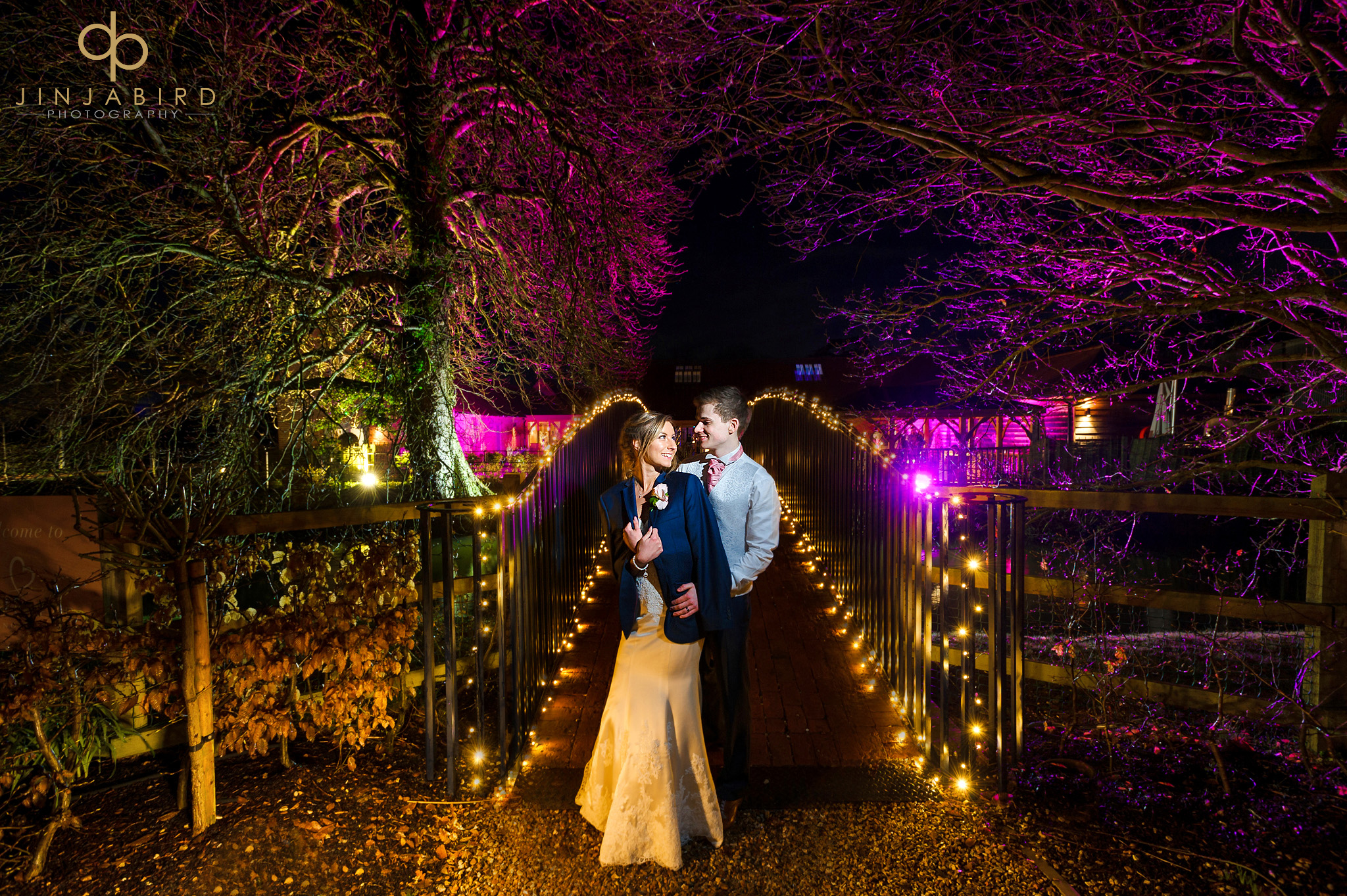 bride and groom on bridge at night bassmead manor barns