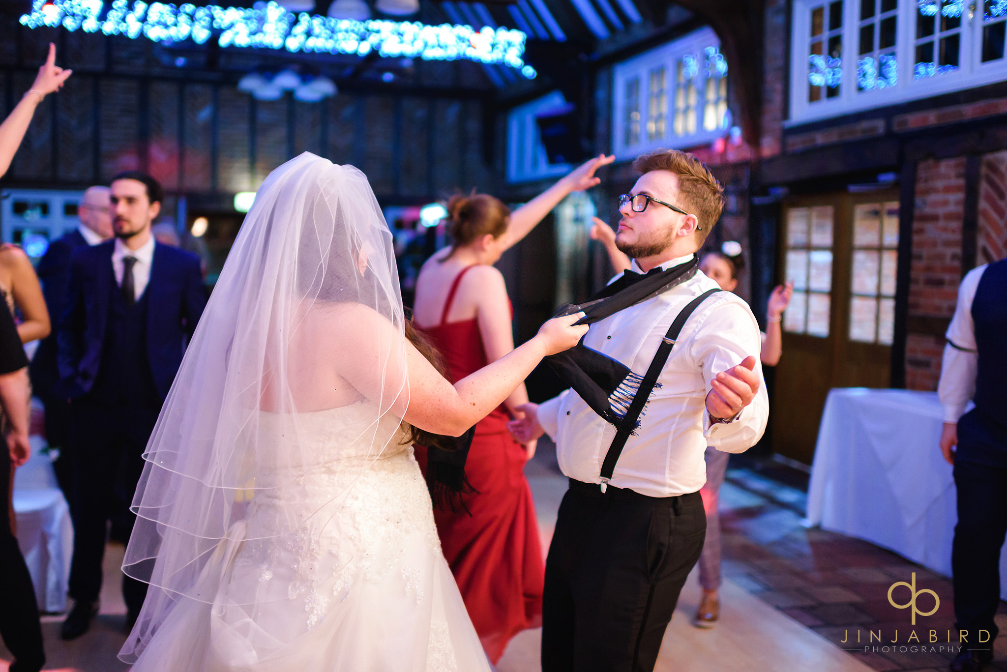 bride pulling grooms tie on dance floor