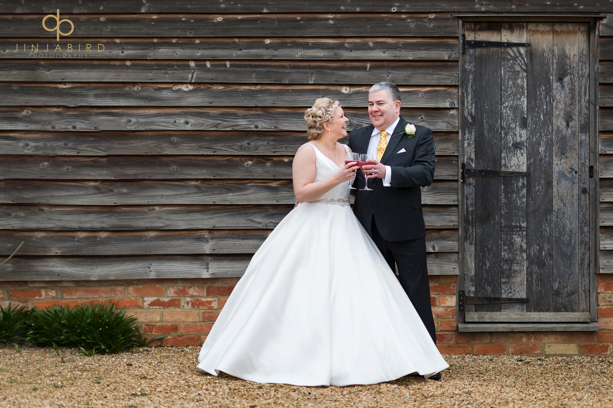 bride toasts groom outside rickety barn bassmead