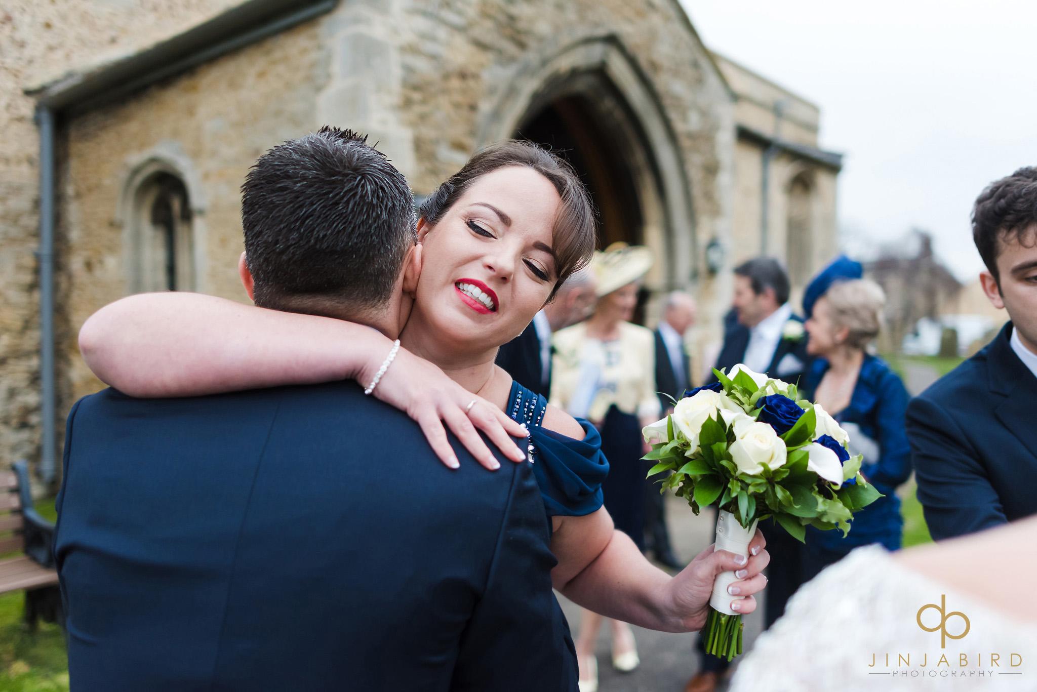 bridesmaid hugging groom