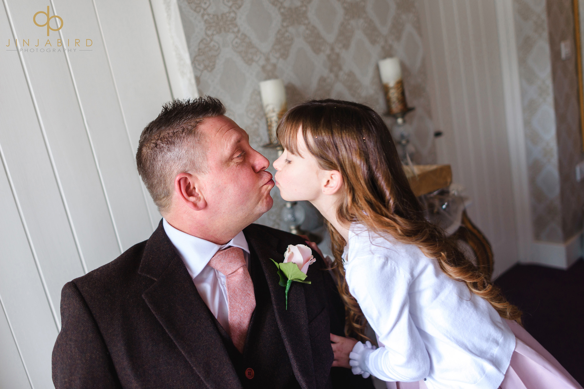 father of bride kissing flower girl