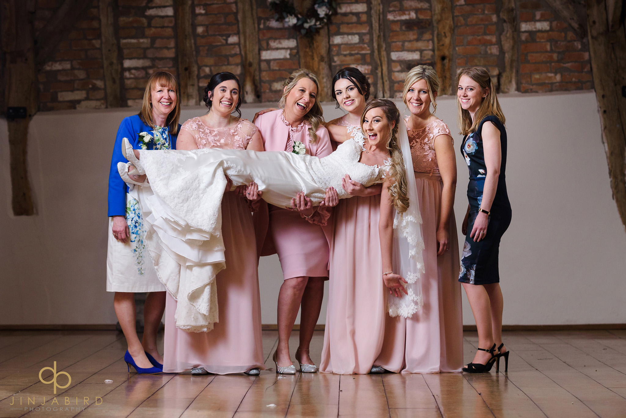 bridesmaids holding bride in air