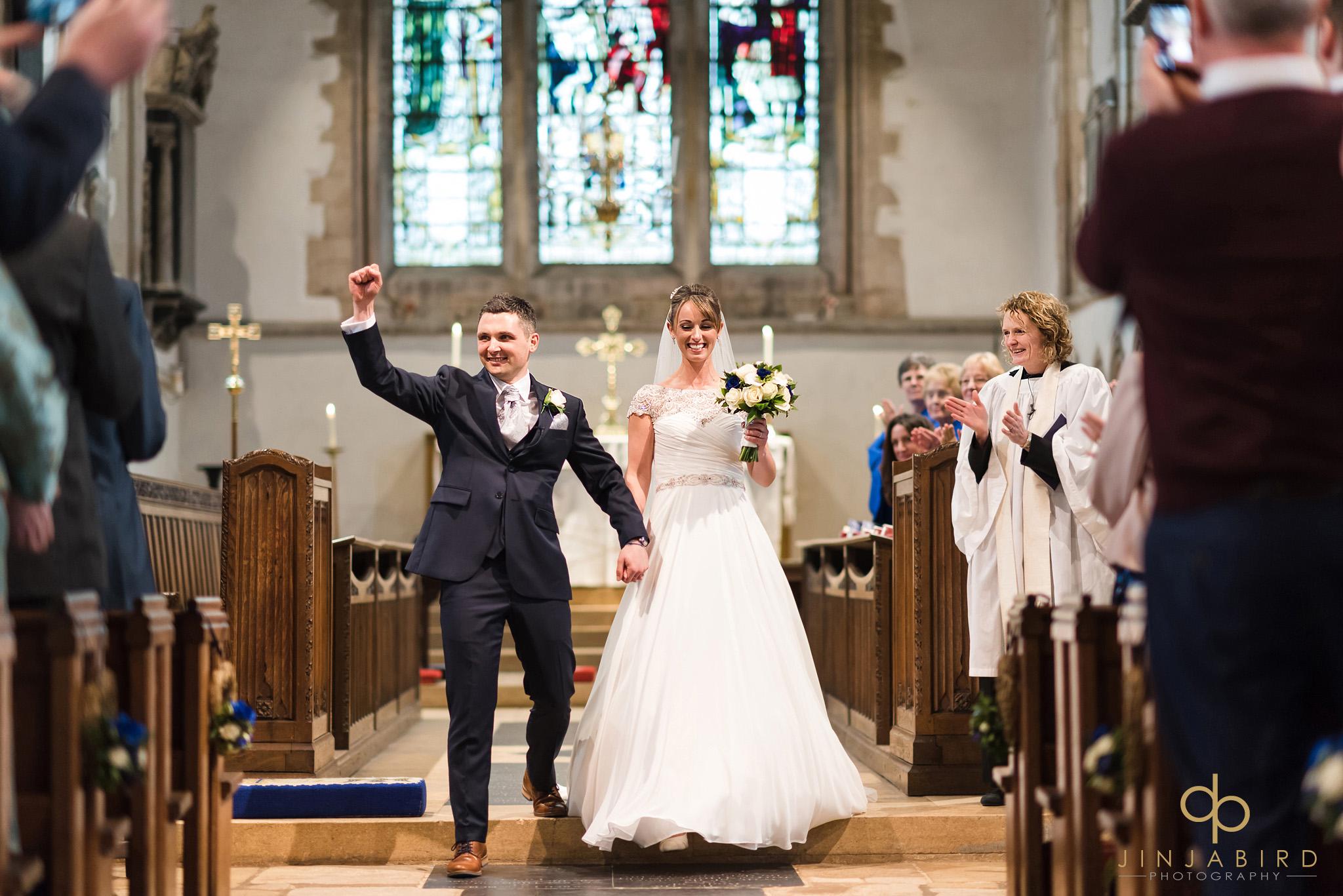 brdie and groom coming down aisle somersham church