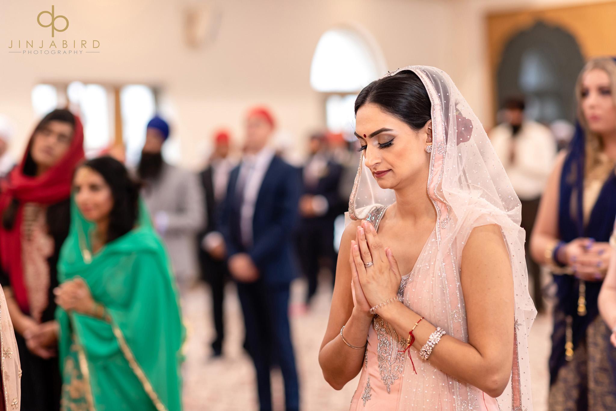 bridesmaid praying in gurdwara