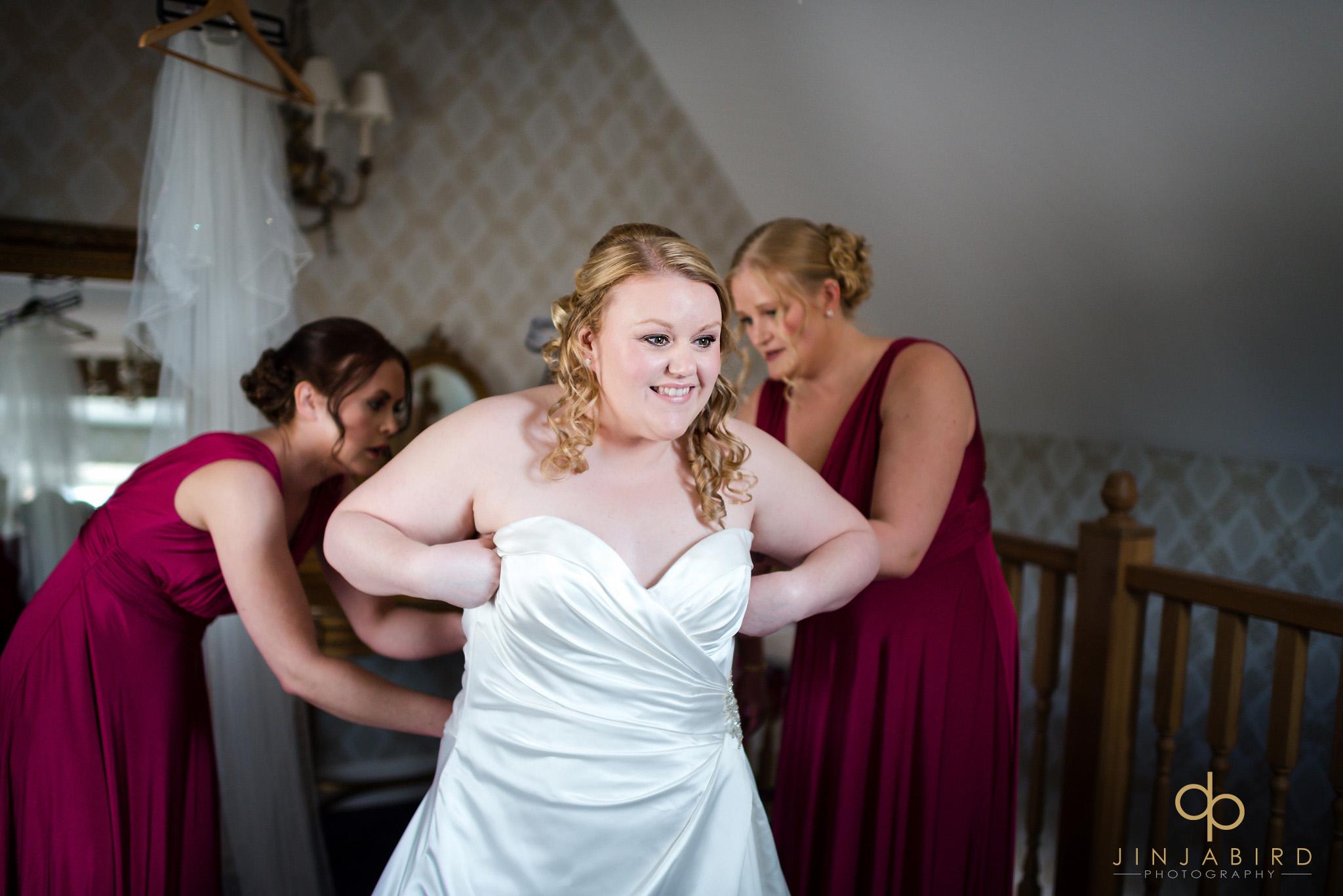 bridesmaids helping bride in dress