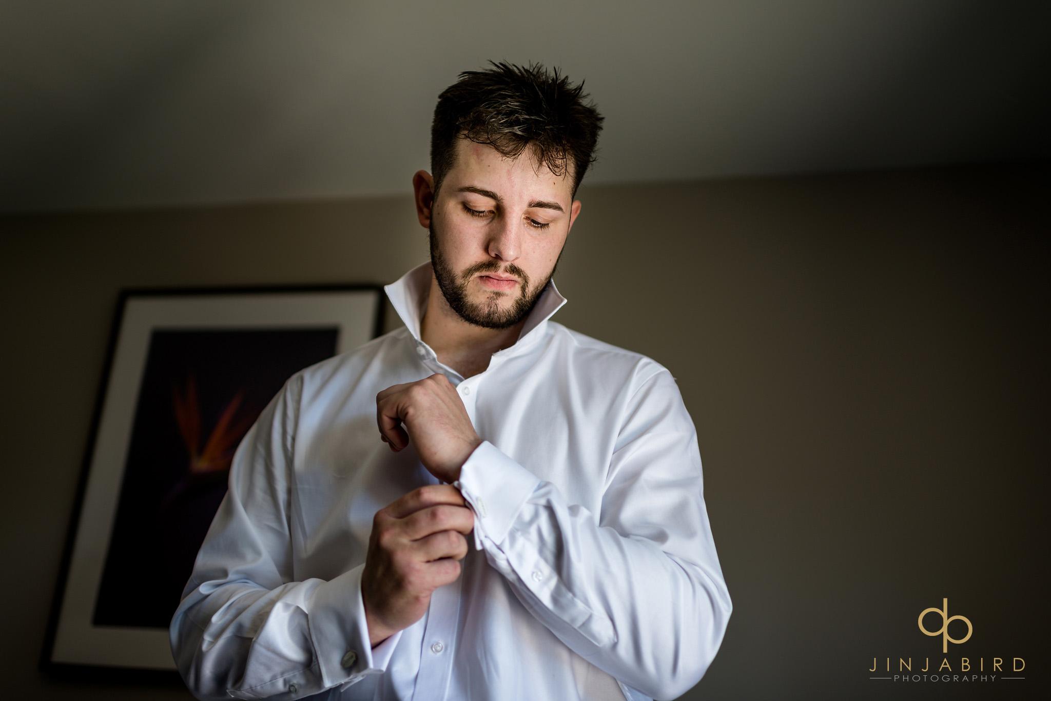 groom putting in cuff links bassmead manor