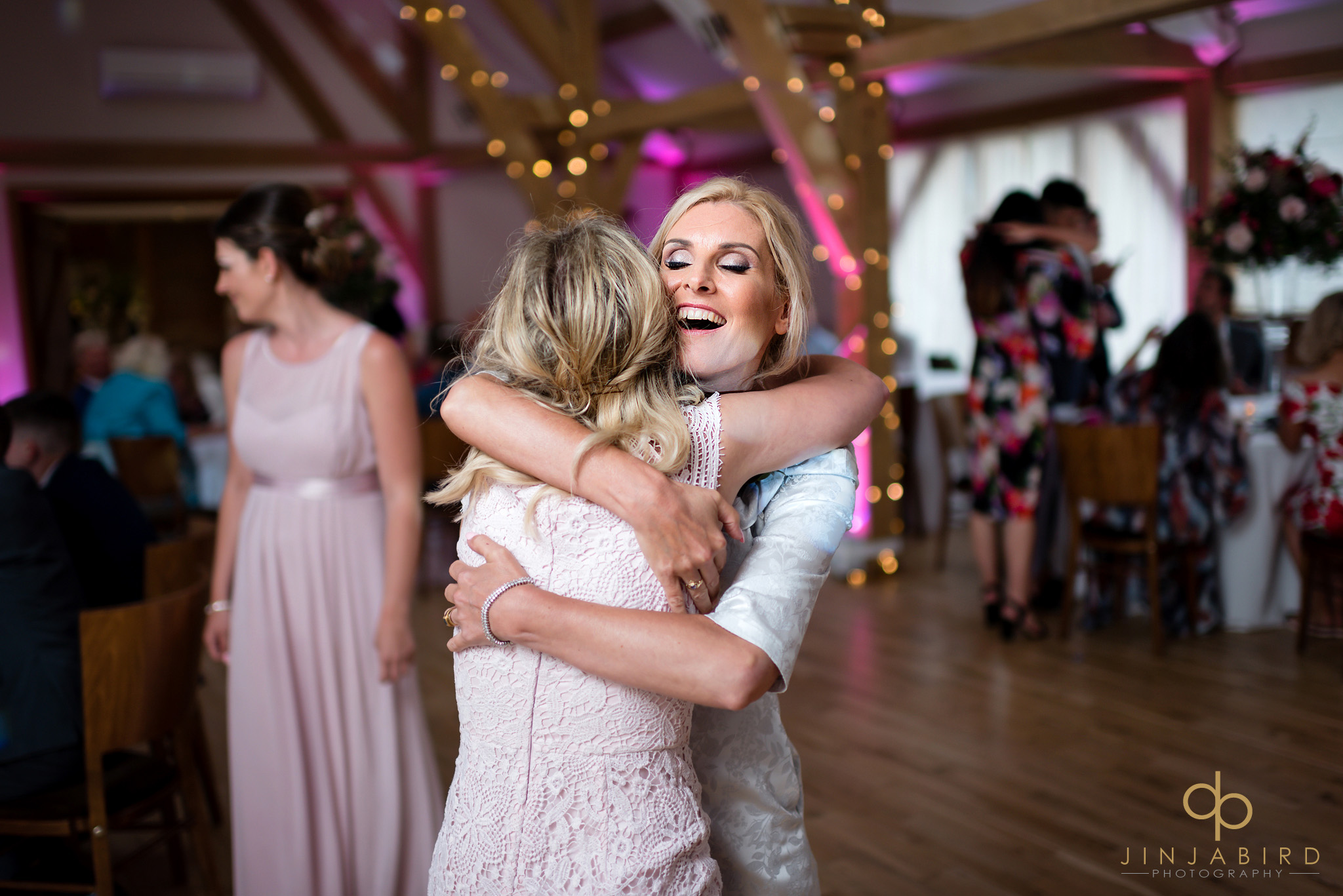 mother hugging bridesmaid