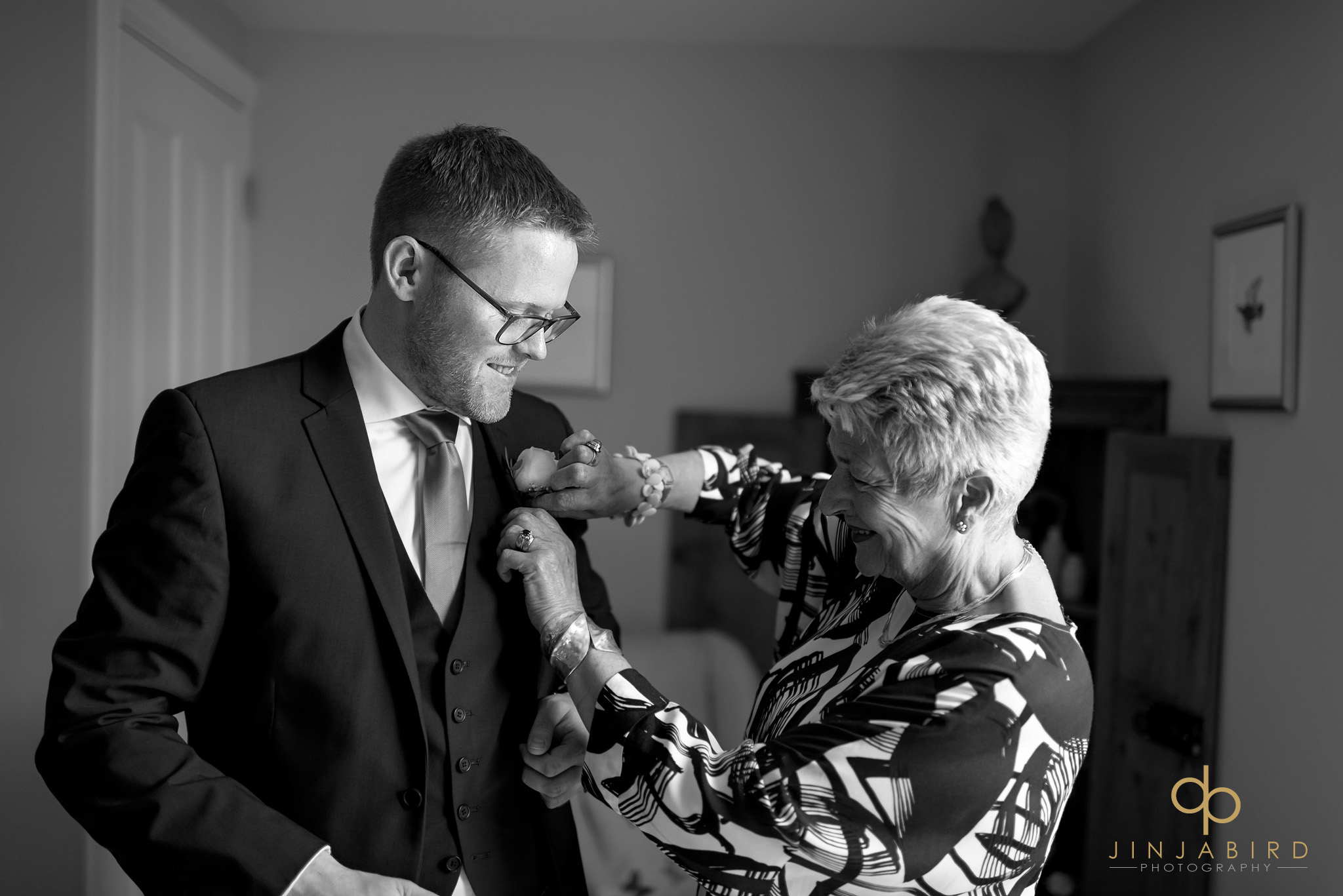 mum putting on grooms button hole
