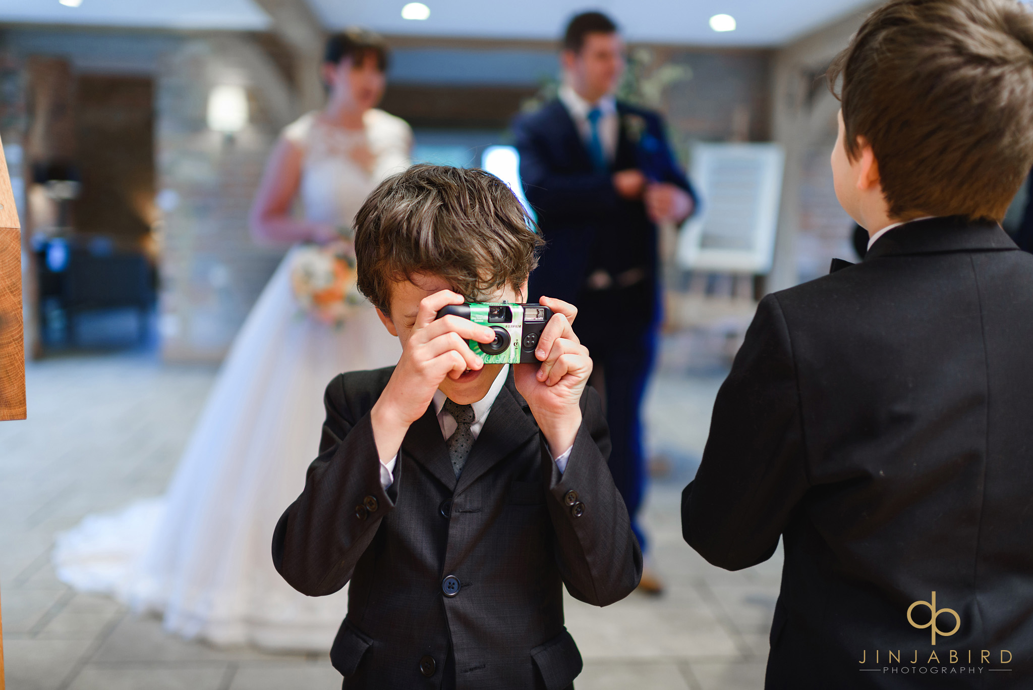 small boy with camera at wedding