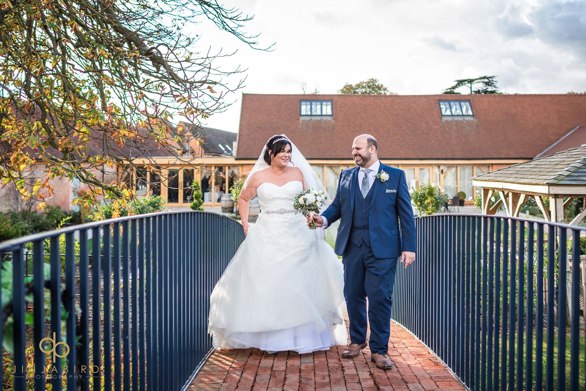 brdie and groom walking over bridge bassmead