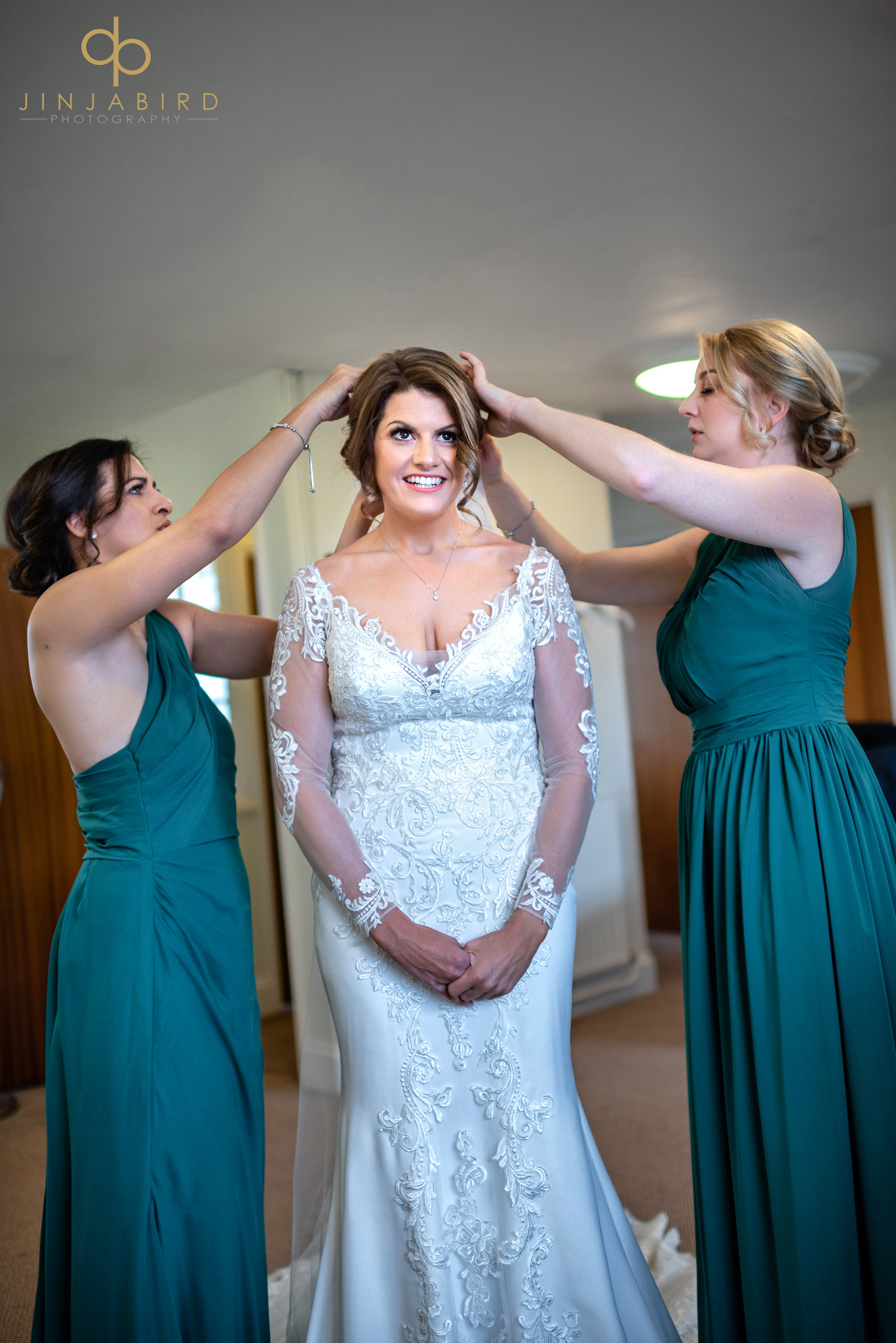 bridesmaids putting in brides veil