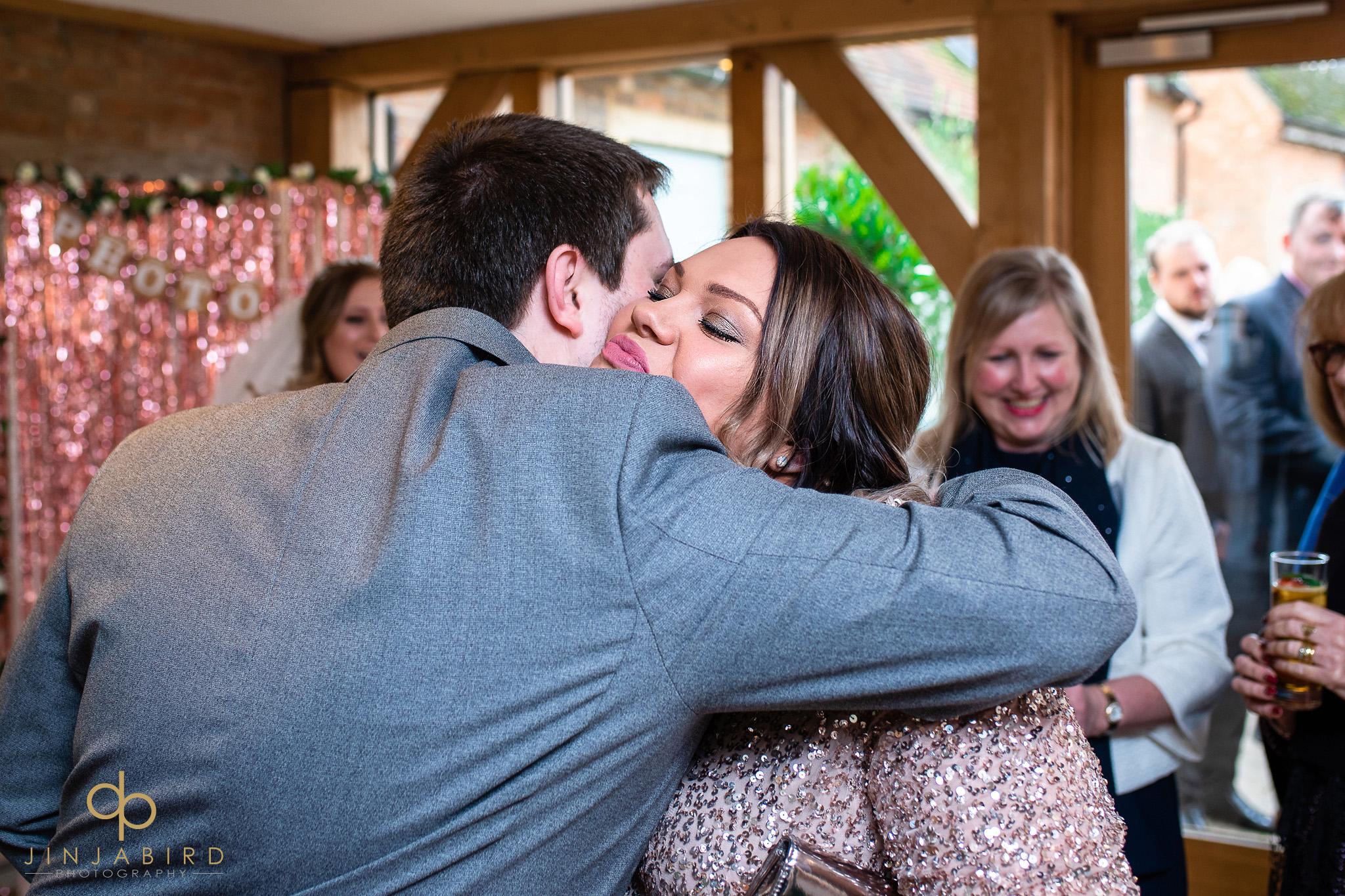 groom hugging bridesmaid