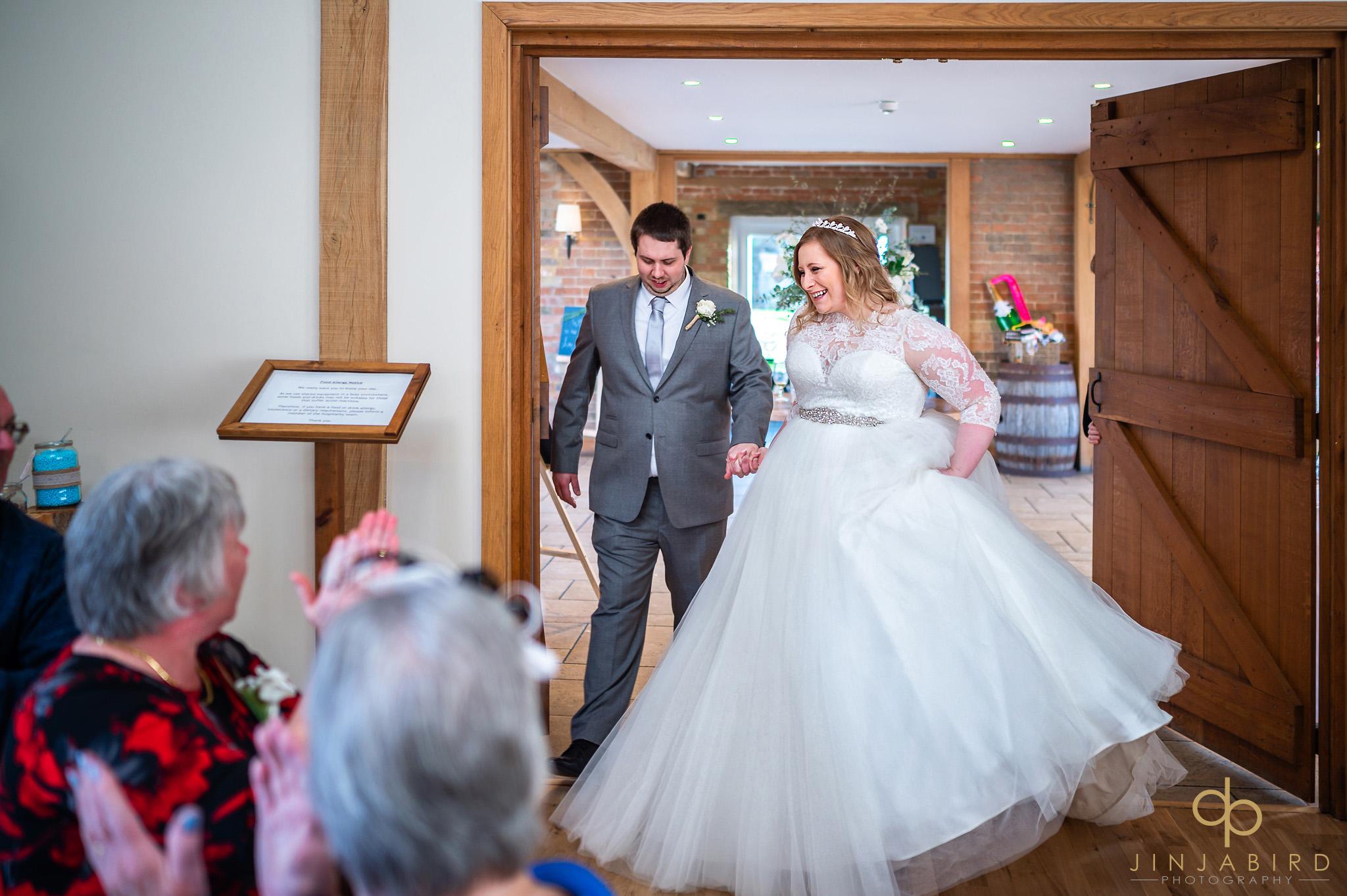 bride with groom entering wedding breakfast