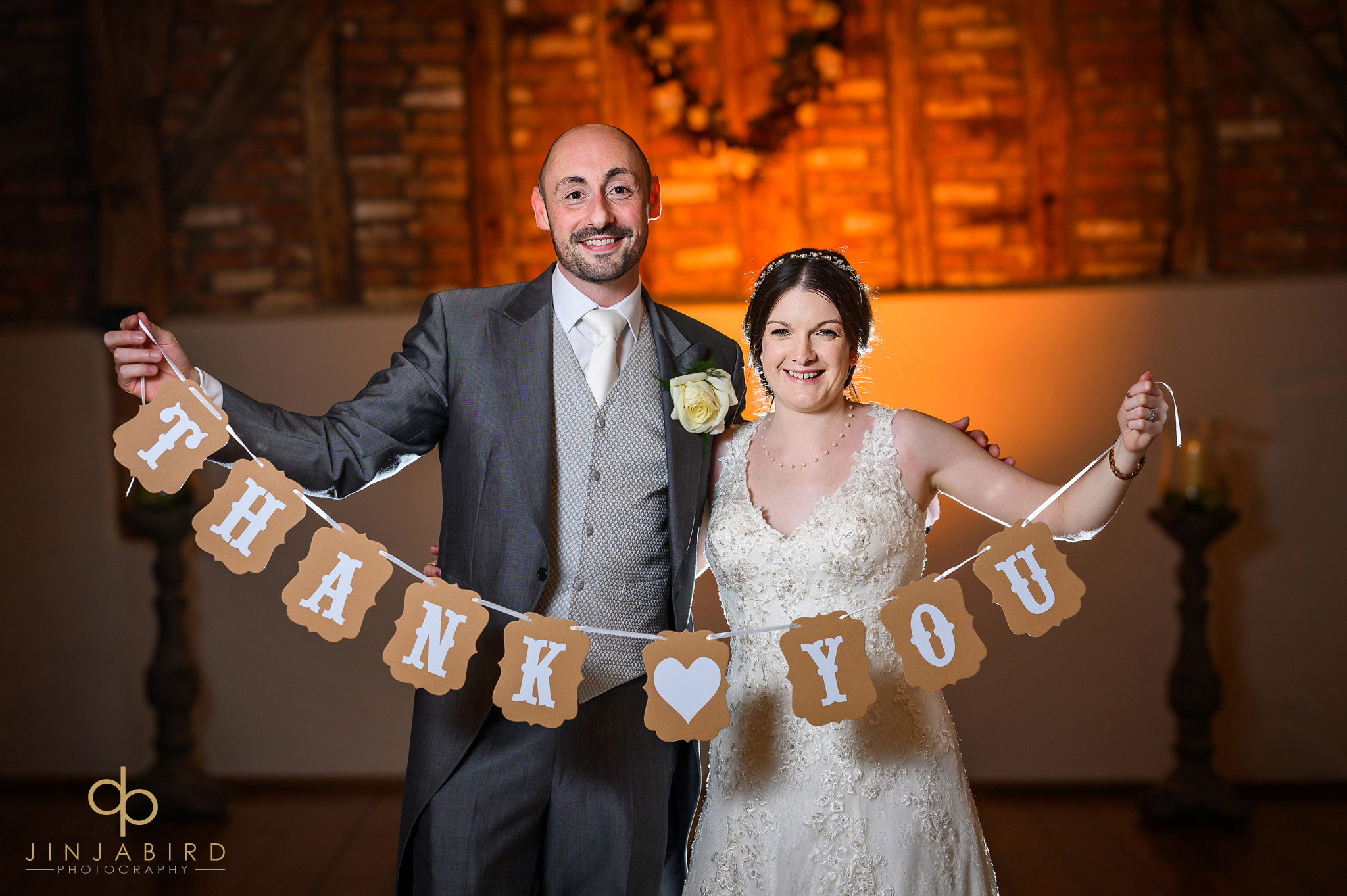 bride and groom with thank you banner