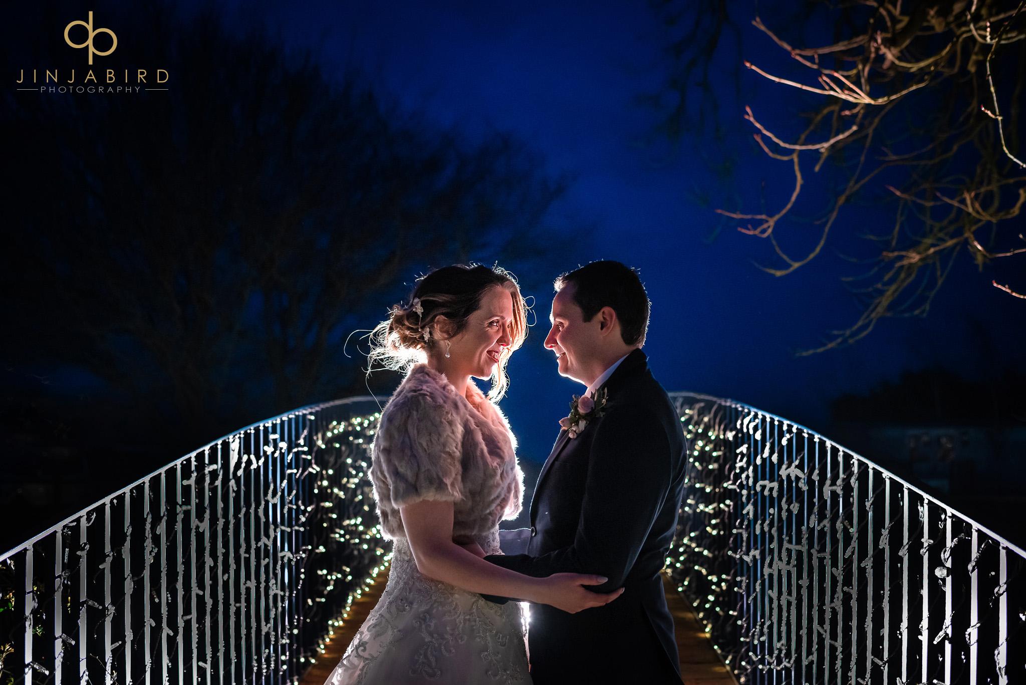 bride with groom on bridge at night bassmead manor