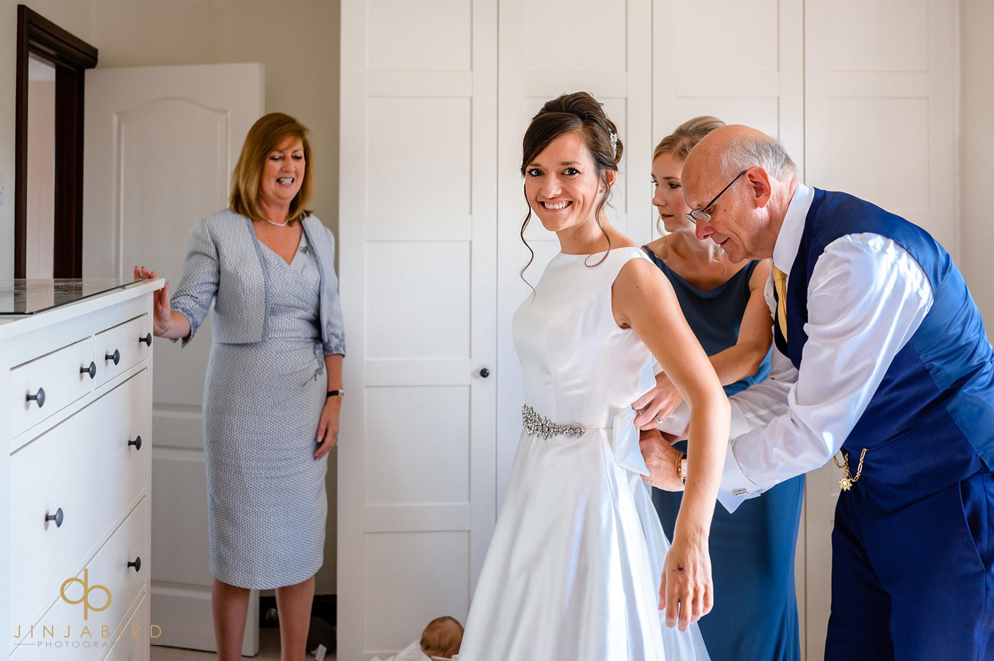 brides dad helping with wedding dress