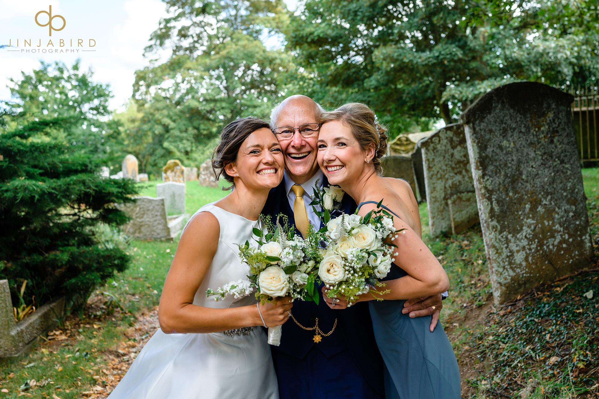 bride and sister hugging dad